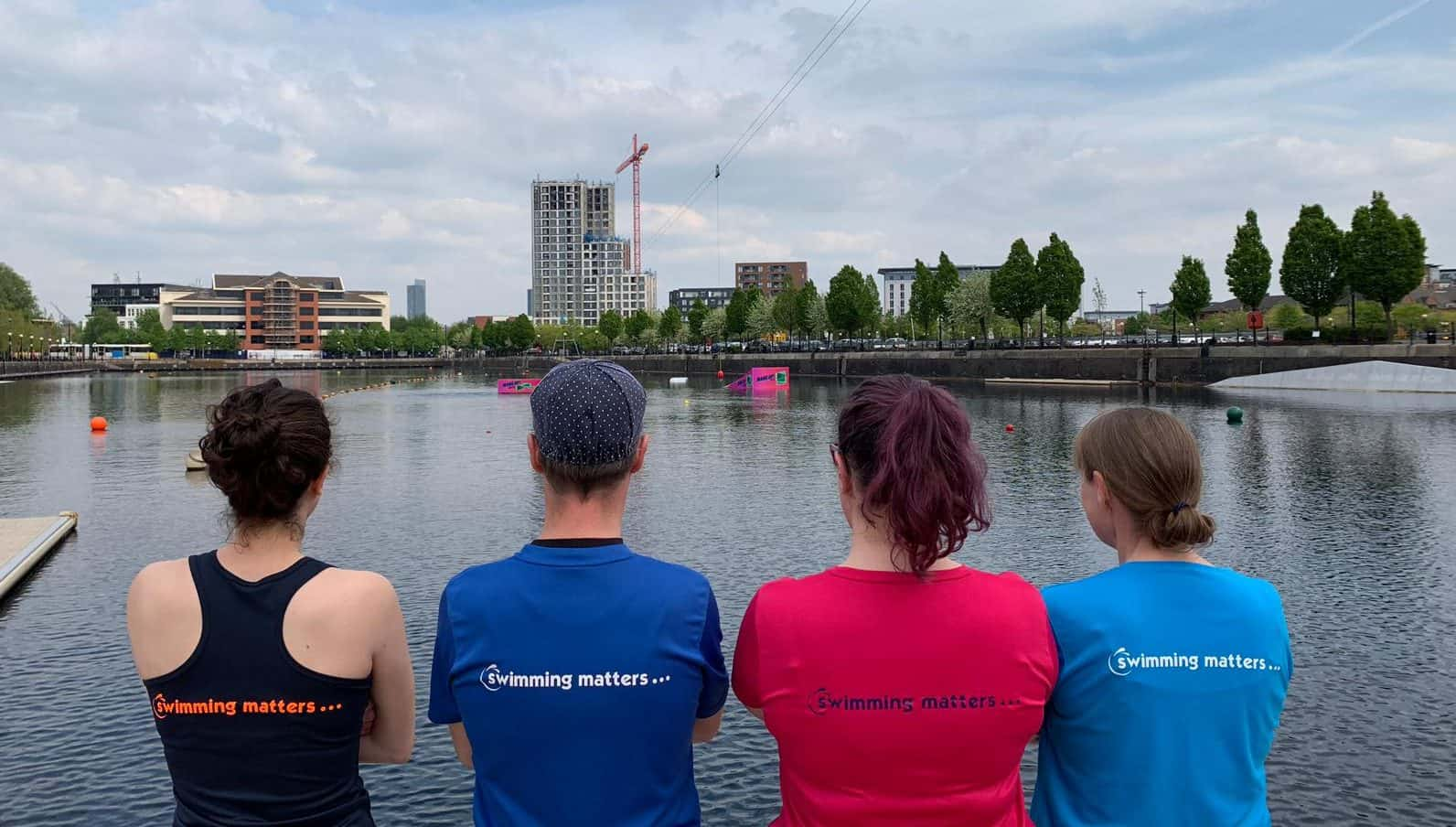 Backs to the camera, 4 swimming matters coaches look over Salford Watersports Centre