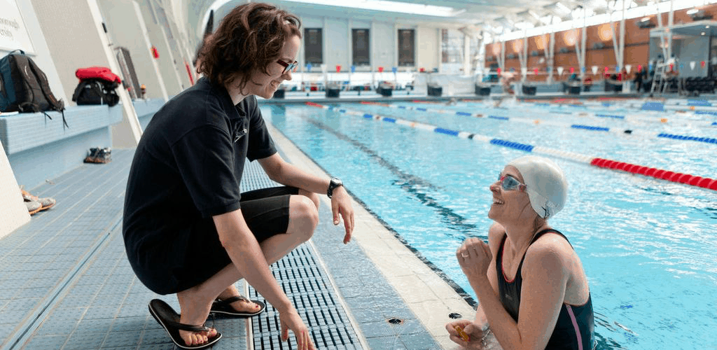 Swimming teacher giving positive feedback to her swimmer